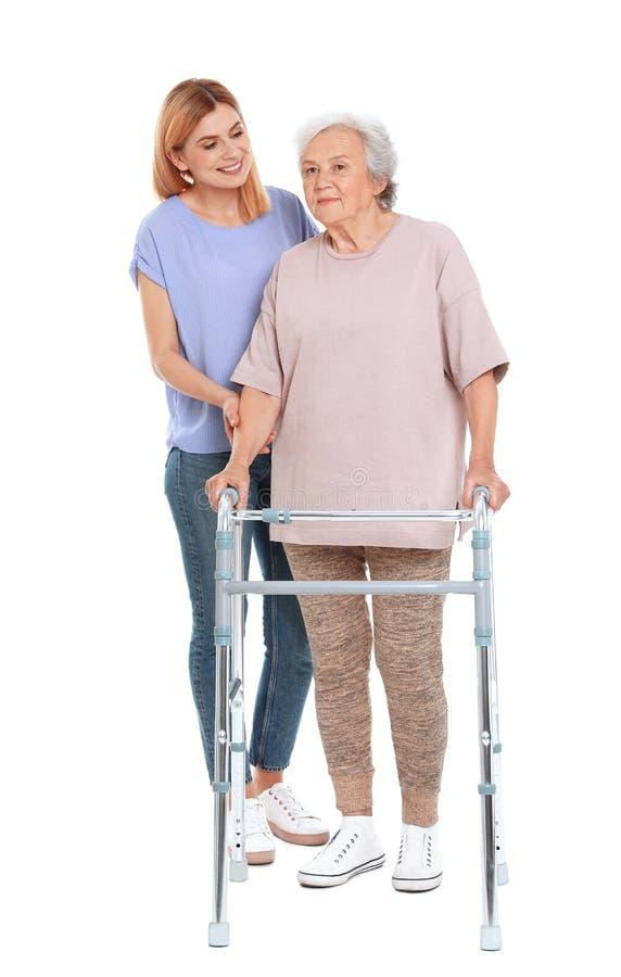 Huisbewaarder die bejaarde met het lopen kader op wit helpen stock afbeelding