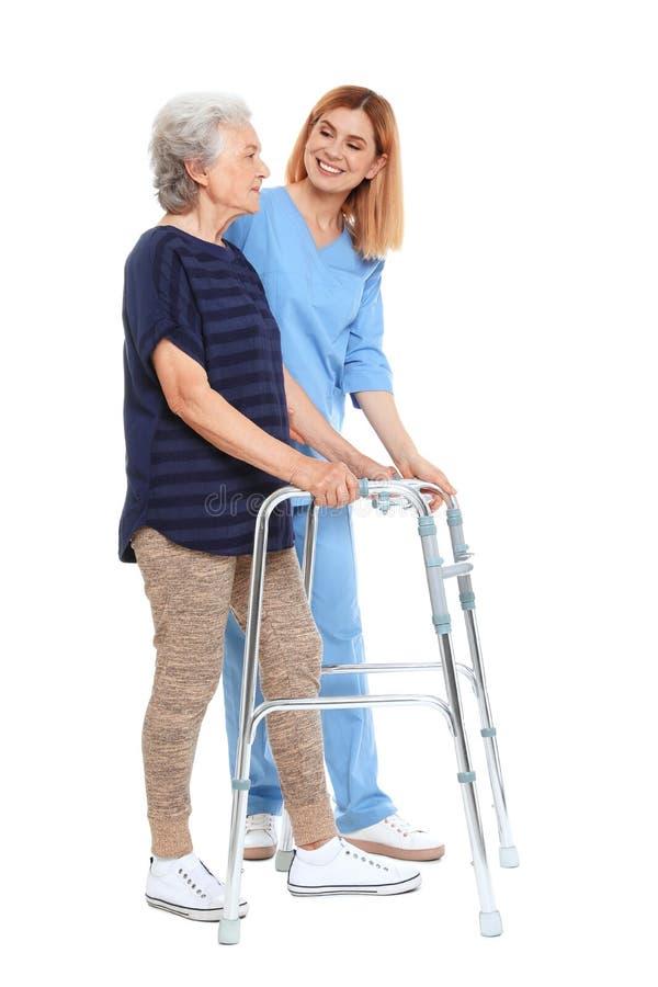 Huisbewaarder die bejaarde met het lopen kader op wit helpen stock foto's