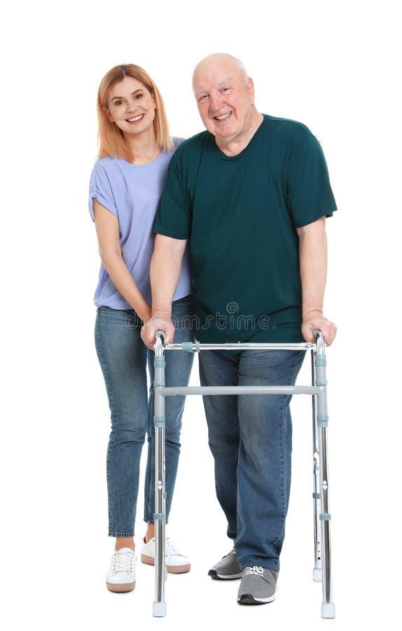 Huisbewaarder die bejaarde met het lopen kader op wit helpen stock fotografie