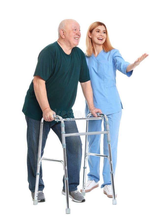 Huisbewaarder die bejaarde met het lopen kader op wit helpen royalty-vrije stock foto
