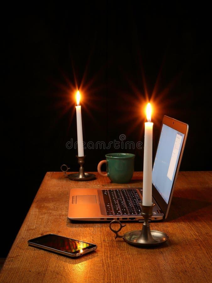 Huisbureau met Laptop door Kaarslicht wordt verlicht dat stock afbeelding
