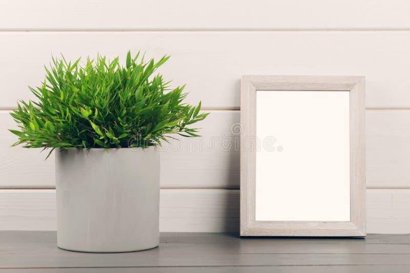 Huisdecoratie - lege omlijsting en bloempot op houten t stock foto's