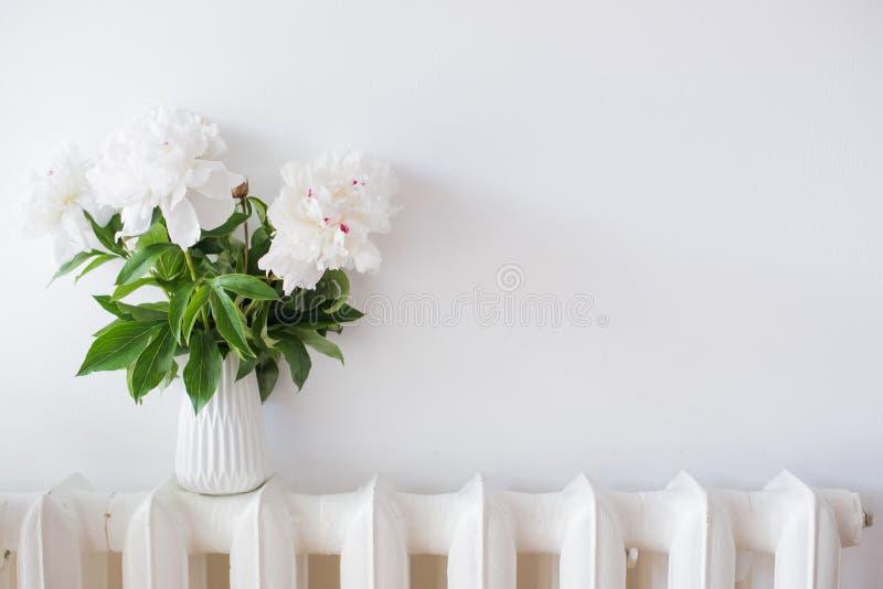 Huisdecoratie, verse pioenen in wit comfortabel ruimtebinnenland met stock afbeelding