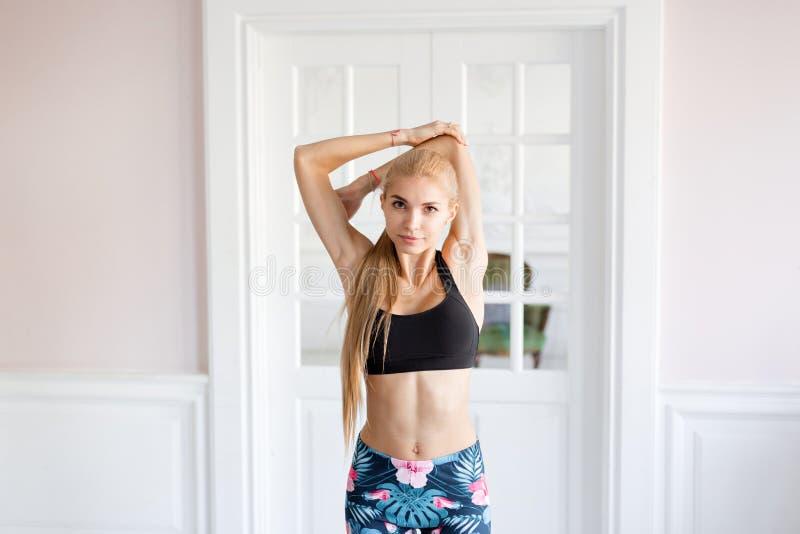 Huisgeschiktheid Jonge vrouw die alvorens op te leiden het doen uitoefent om haar spieren en verbindingen uit te rekken opwarmen  stock afbeeldingen