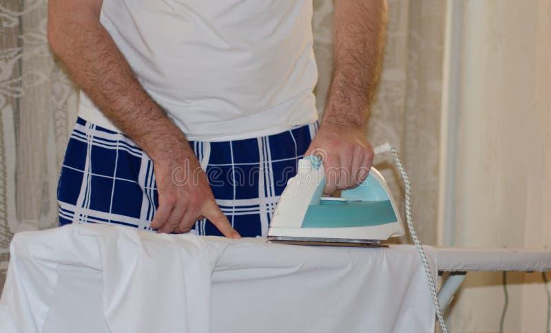 jonge mens het strijken t shirt met elektrisch ijzer stock