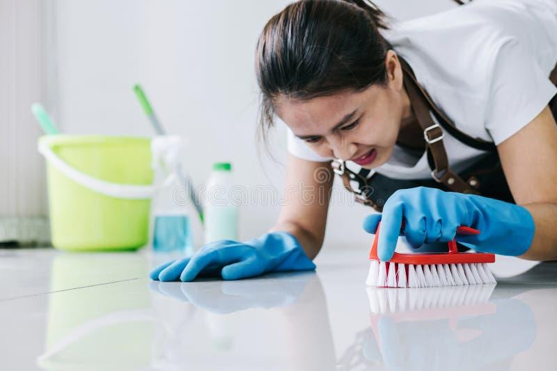 Huishouden en het schoonmaken concept, Gelukkige jonge vrouw in blauwe oneffenheid stock afbeeldingen