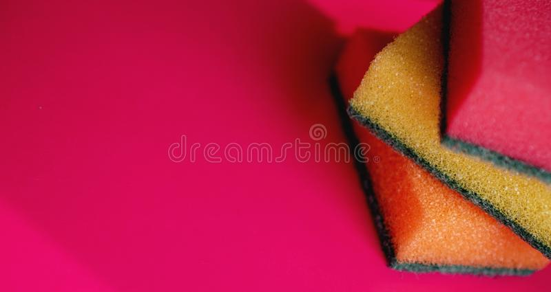 Huishouden het schoonmaken concept Kleurrijke sponsen op roze achtergrond stock foto's