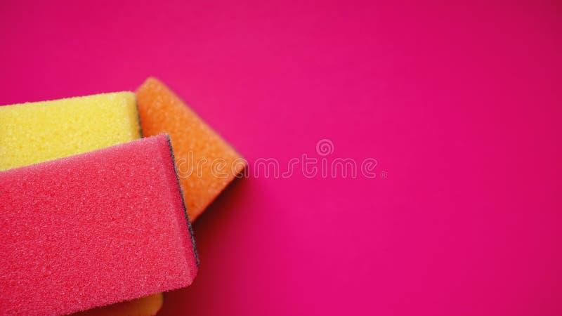 Huishouden het schoonmaken concept Kleurrijke sponsen op roze achtergrond stock foto