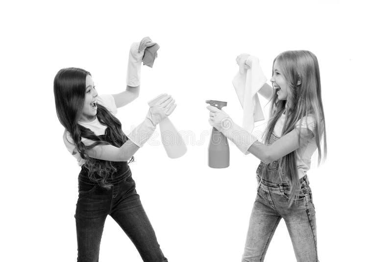 Huishoudenplichten Weinig Helper Meisjes leuke jonge geitjes die rond met mistspuitbus schoonmaken Houd het schoon Zustersrivalit stock fotografie