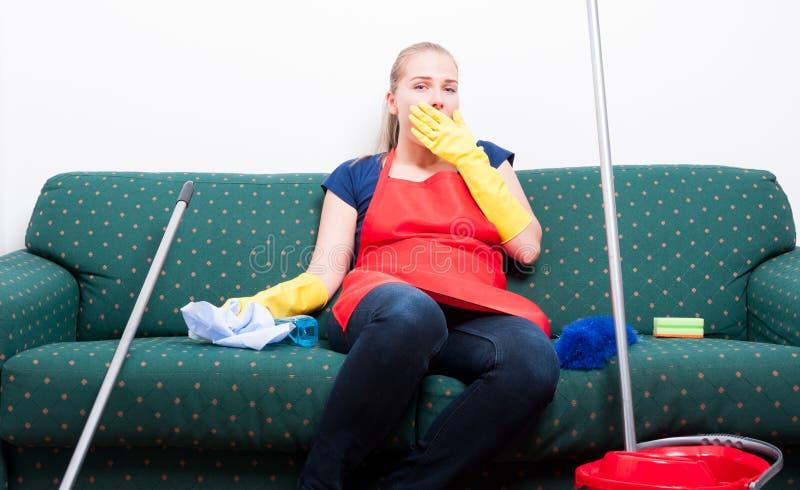 Huishoudster die een onderbreking van het schoonmaken van de ruimte nemen royalty-vrije stock foto