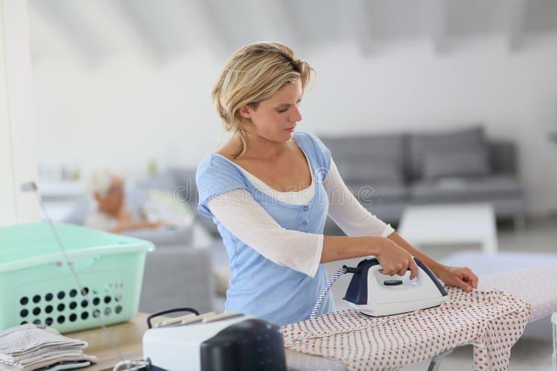 Huishoudster het strijken kleren stock foto