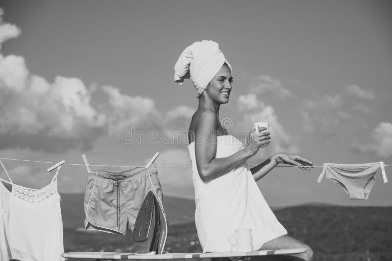 huishoudster vrouwenhuisvrouw in de koffiekop van de handdoekgreep bij drooglijn stock afbeeldingen