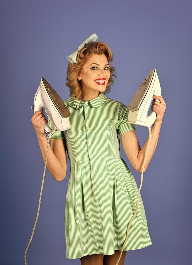 Huishoudstervrouw het strijken op blauwe Huishoudster als achtergrond in eenvormig met ijzer, huishouden stock foto's