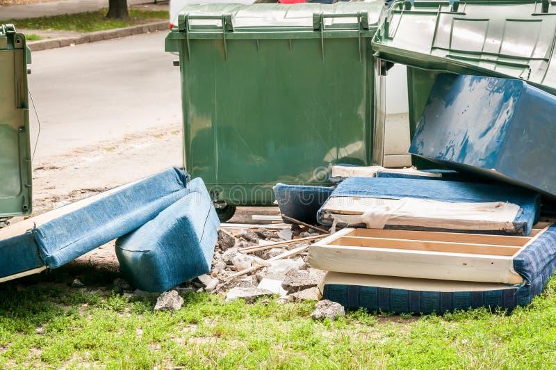 Huismeubilair in de troep dichtbij straatvuilnisbakken wordt weggegooid in de stad na ramp die stock fotografie