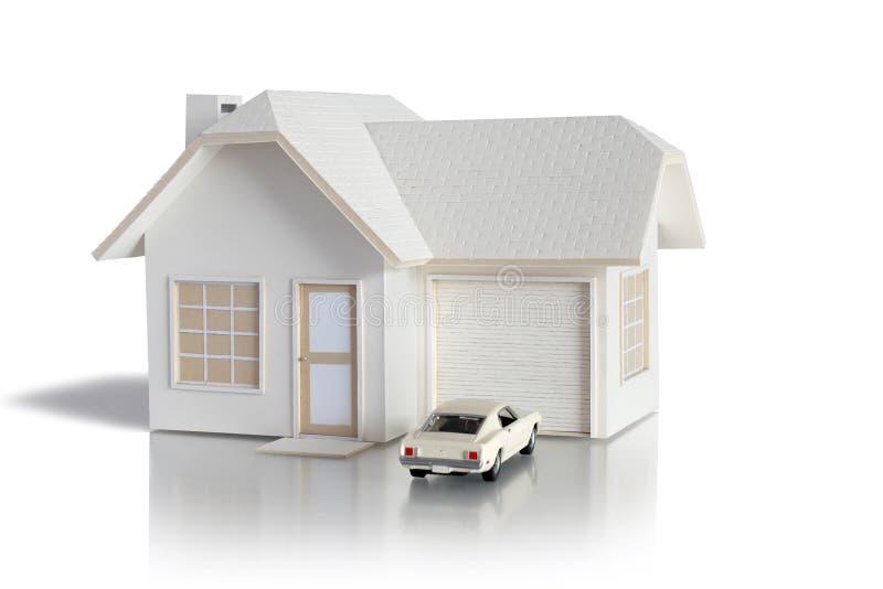 Huisminiatuur met auto op witte achtergrond voor onroerende goederen wordt ge?soleerd en bouwconcepten dat Huis miniatuur ontworp stock foto