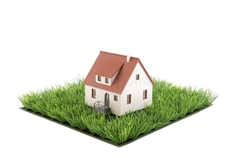Huisminiatuur op vierkant van groen grasgebied stock foto