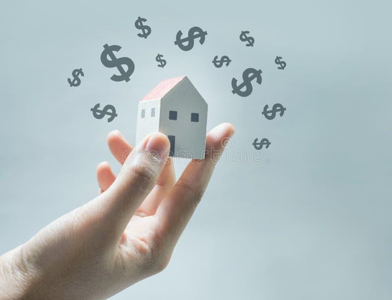 Huismodel op menselijke handen met dollarpictogram Onroerende goederen besparingengeld, stock afbeelding