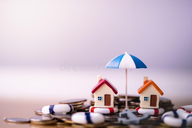 Huismodel in reddingsboeien op muntstukkenstapel stock afbeelding