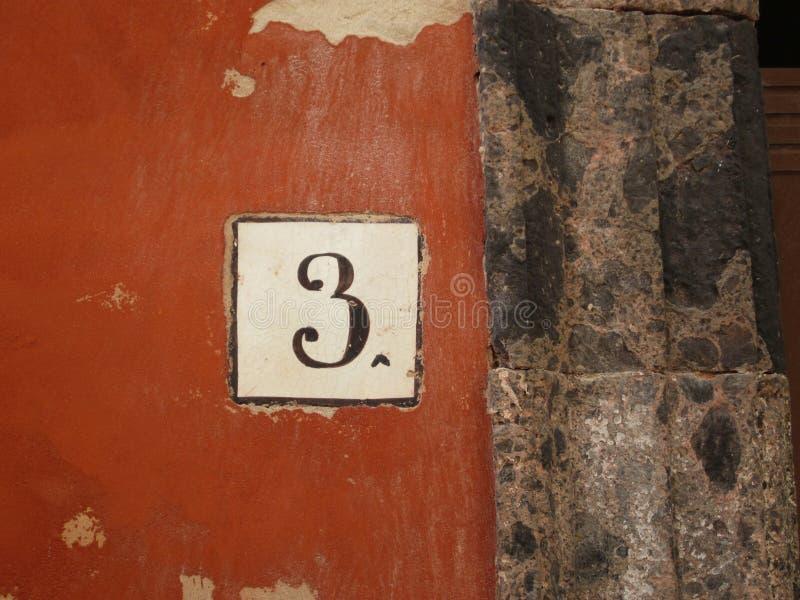 Huisnummer drie op een siena rode muur van een huis in Procida Ita stock afbeeldingen