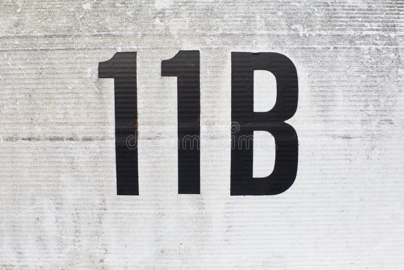 Huisnummer elf B in een steenmuur die wordt gegraveerd stock foto's