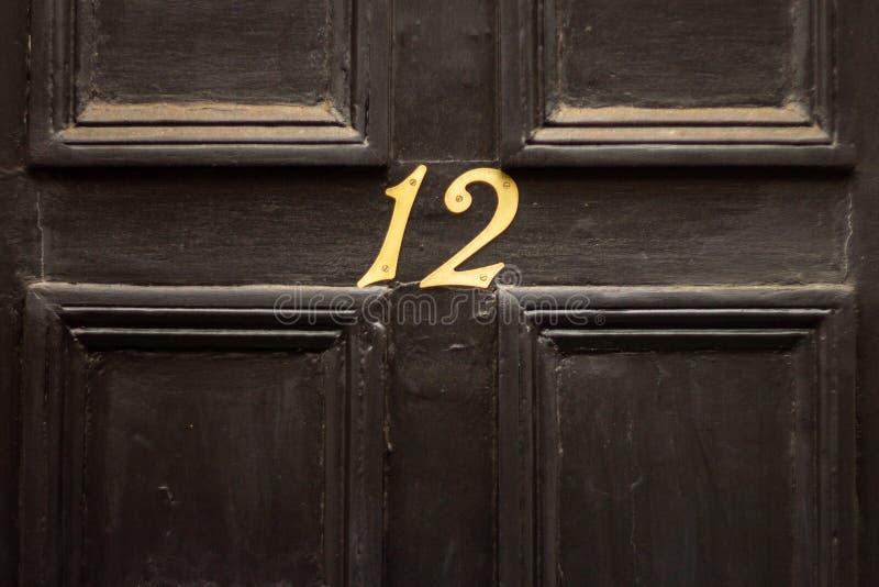 Huisnummer 12 op een zwarte stoffige voordeur in Groot-Brittannië stock foto