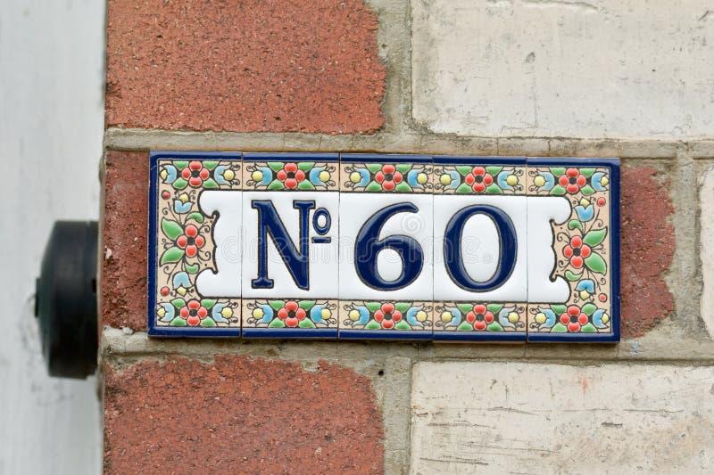 Huisnummer 60 teken in keramische tegels stock foto