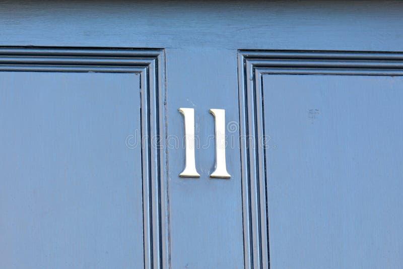 Huisnummer 11 teken op blauwe houten deur stock afbeelding