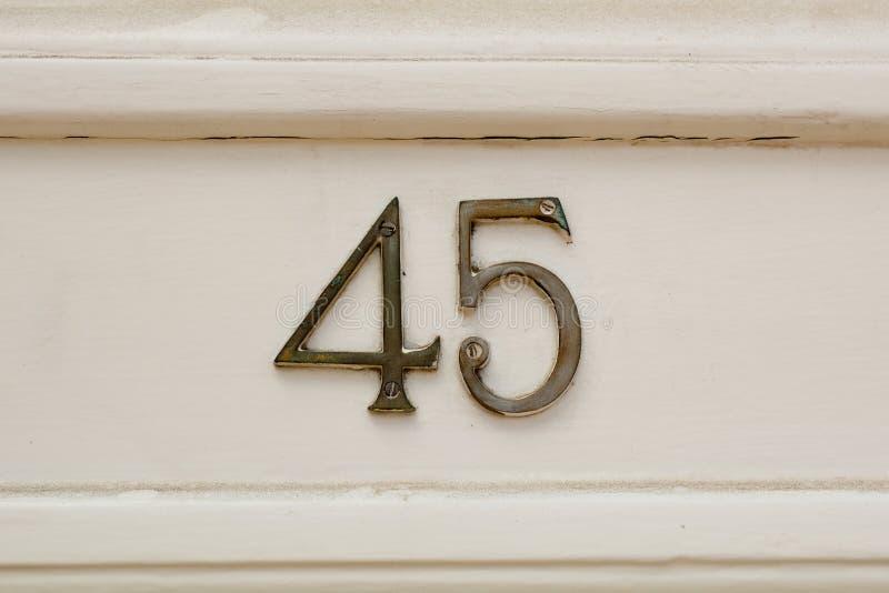 Huisnummer 45 teken op deur stock foto