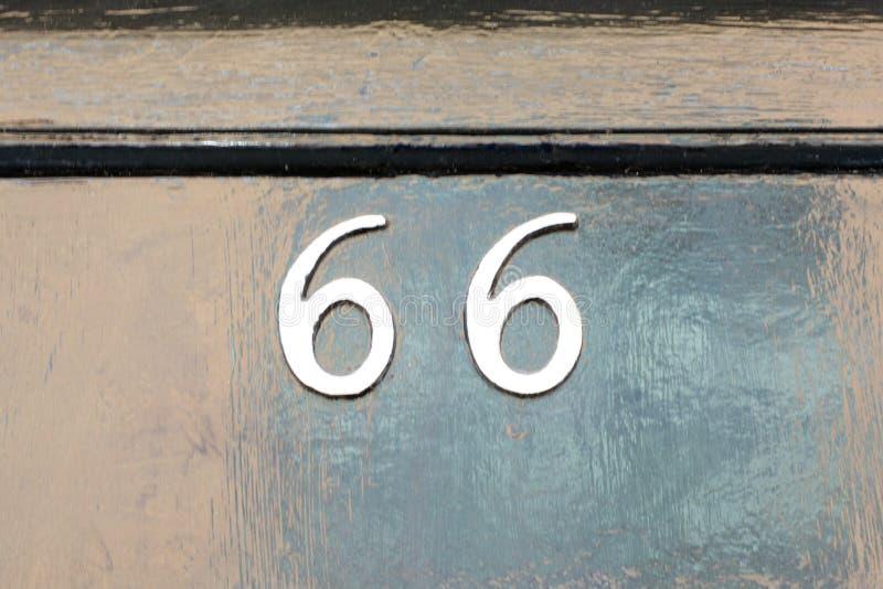 Huisnummer 66 teken op deur stock fotografie