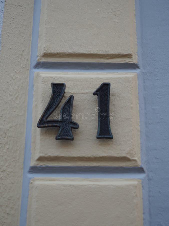 Huisnummer 41, zwarte aantallen op een room-gekleurde muur stock afbeelding