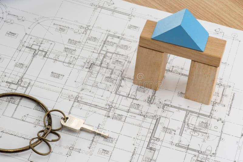 Huisplan met stuk speelgoed houtsnedemodel en een sleutel met uitstekende ring royalty-vrije stock afbeeldingen