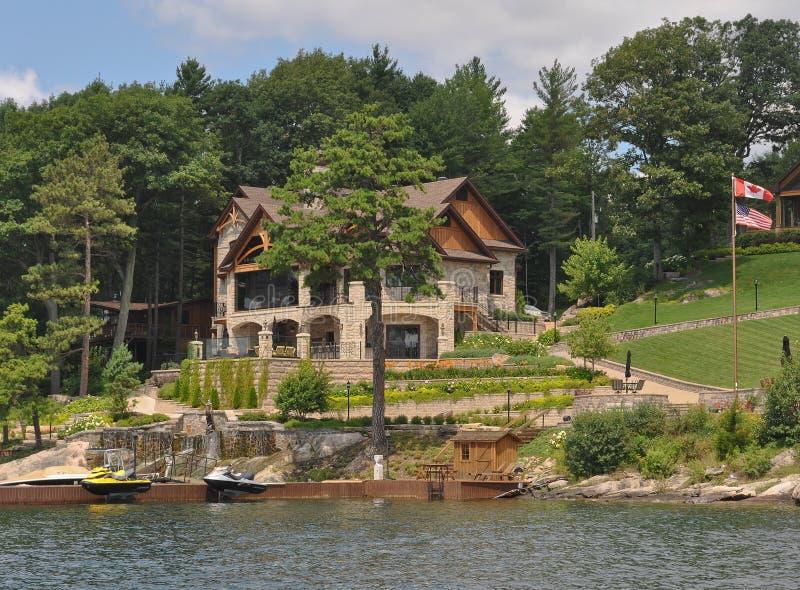 Huisplattelandshuisje in Duizend Eilanden met Canadese en Amerikaanse Vlaggen royalty-vrije stock afbeeldingen