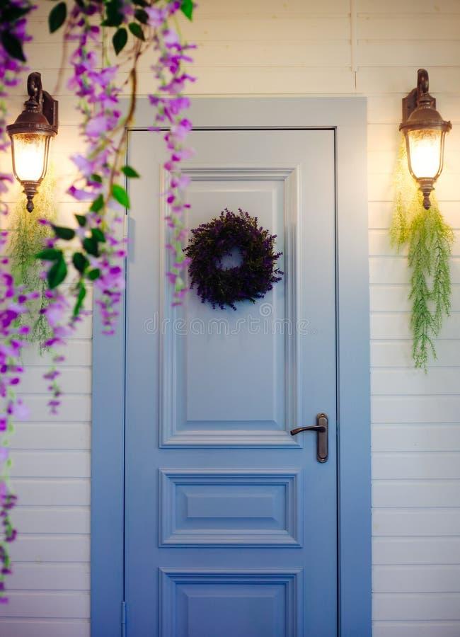 Huisportiek met een een lantaarn, een blauwe deur en decoratie van wisteriabloemen royalty-vrije stock foto