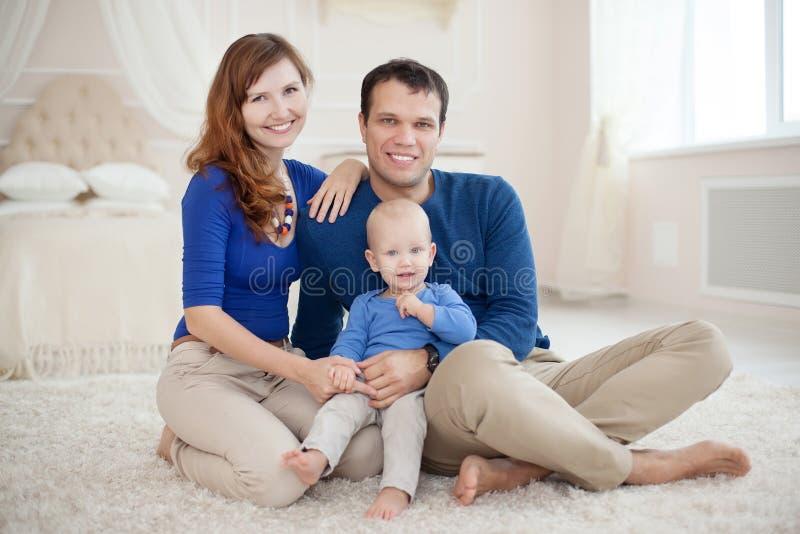 Huisportret van gelukkige jonge familie stock foto's