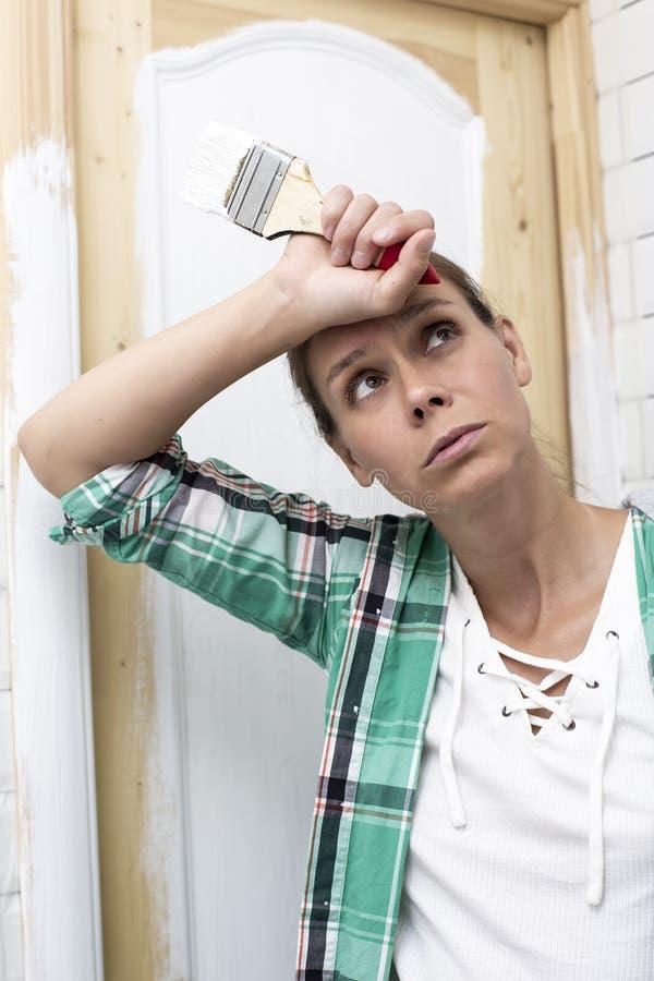 Huisreparatie De gemartelde die vrouw wordt vermoeid om de houten deur in de badkamers in wit en holding te schilderen van hem di stock foto