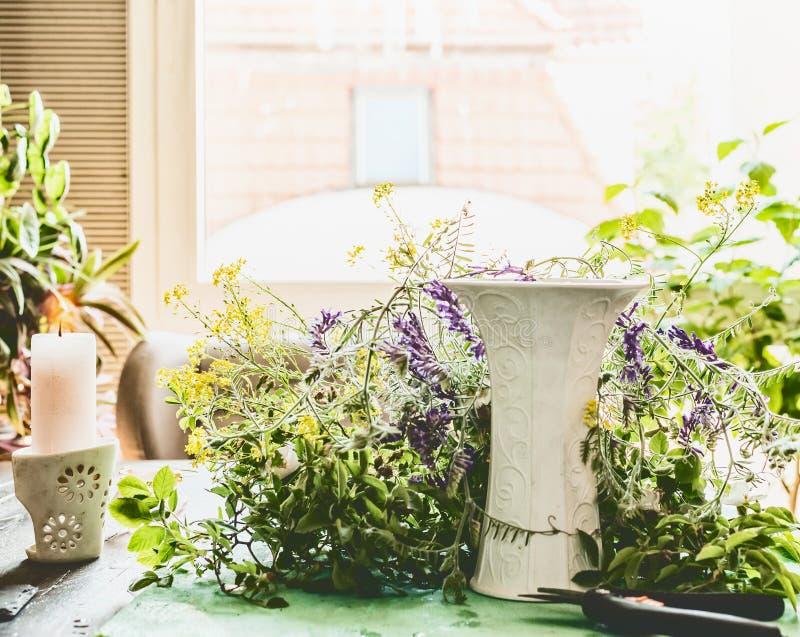 Huisscène voor het maken van een de zomerboeket voor een woonkamer met wilde bloemen en een vaas stock fotografie