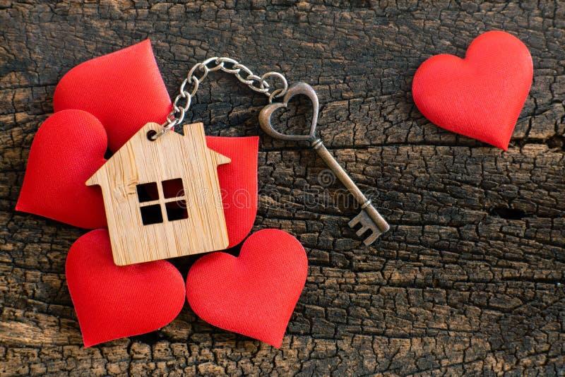 Huissleutel in hartvorm met huissleutelring op houten die achtergrond met miniharten wordt verfraaid stock afbeelding