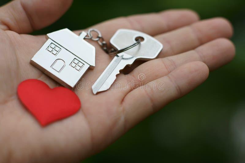 Huissleutel met de sleutelring van het liefdehuis en rood minihart op hand, zoet huis die, concept geven stock foto