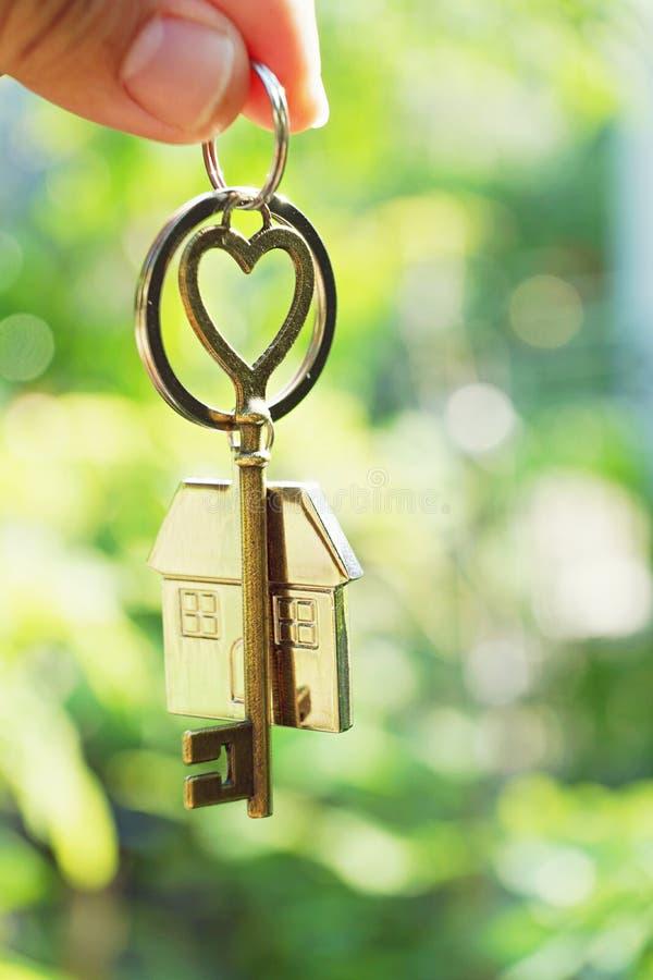 Huissleutel met de sleutelring van het liefdehuis het hangen met de achtergrond van de onduidelijk beeldtuin royalty-vrije stock fotografie