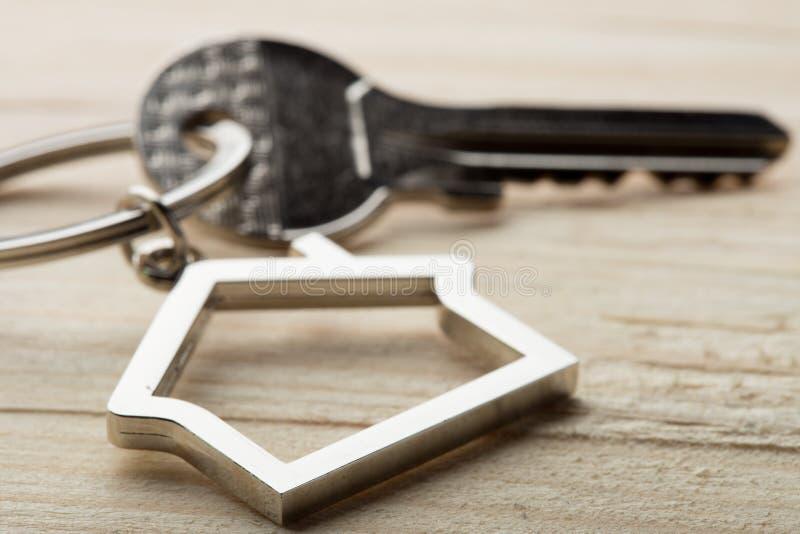 Huissleutel met een keychain op houten bureauconcept voor onroerende goederen stock afbeelding