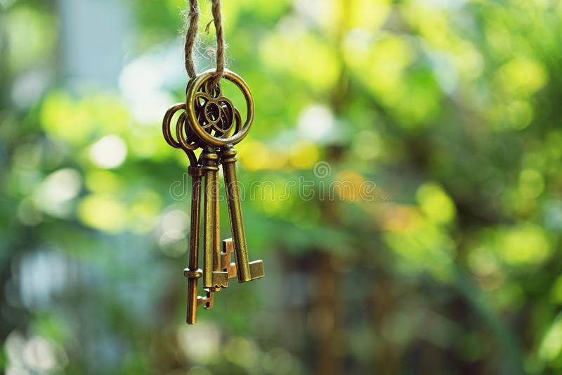 Huissleutel met huissleutelring het hangen met de achtergrond van de onduidelijk beeldtuin stock foto