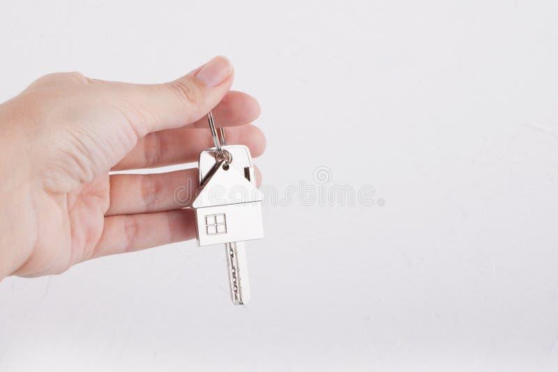 Huissleutel met trinket huis in de vrouwelijke palm Huurlandgoed royalty-vrije stock fotografie