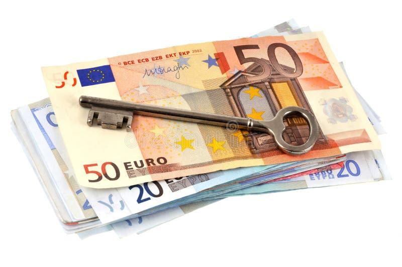 Huissleutel op een pakje van bankbiljetten wordt geplaatst dat royalty-vrije stock afbeeldingen