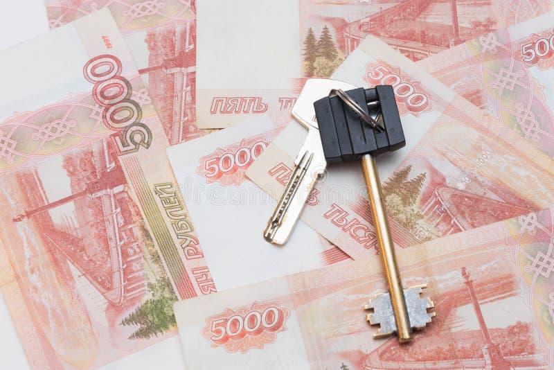 Huissleutels op de achtergrond van vijf duizend roebelsbankbiljetten Aankoop van onroerende goederen Reis en geld Flataankoop stock fotografie