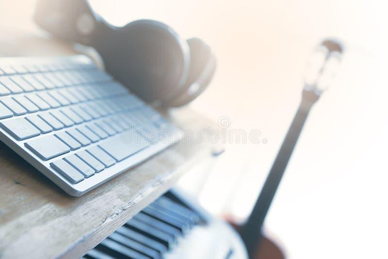Huisstudio met een gitaar, een piano en een computer voor het mengen van audio royalty-vrije stock fotografie