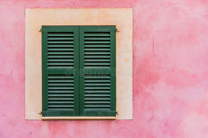 Huisvenster en rozerode gekleurde pleistermuur stock afbeeldingen