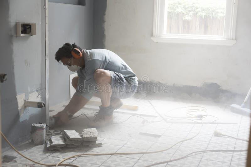 Huisvernieuwer die machtshulpmiddelen met behulp van die in een muur snijden stock foto's