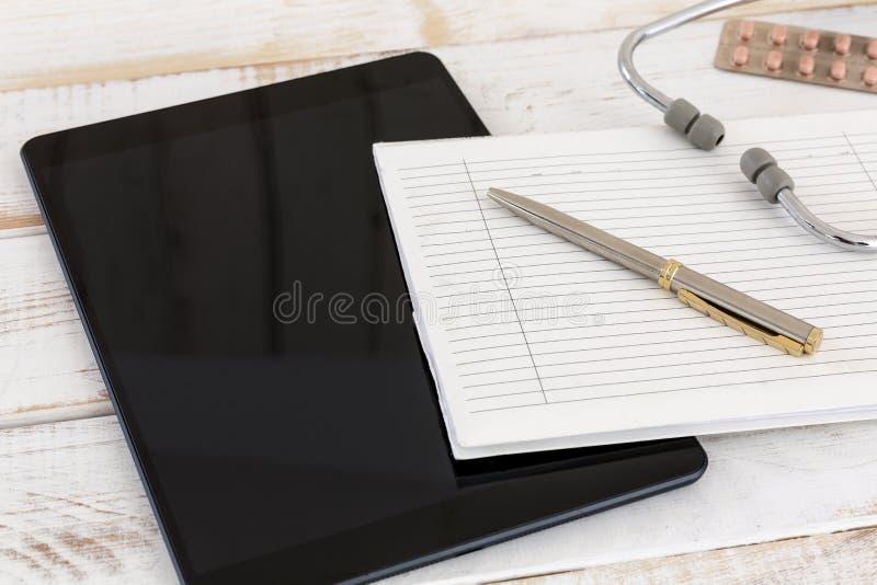 Huisvraag, het bezoek van de arts, elektronische documentatie, geschreven documentatie, tablet met organisator en stethoscoop stock afbeelding