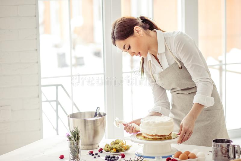 Huisvrouw die cake behandelen met room Sluit omhoog zijaanzichtfoto royalty-vrije stock afbeelding