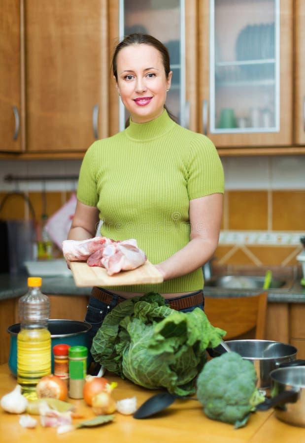 Huisvrouw die maaltijd thuis voorbereiden stock foto's
